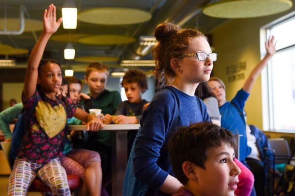 children in a classroom raising their hand