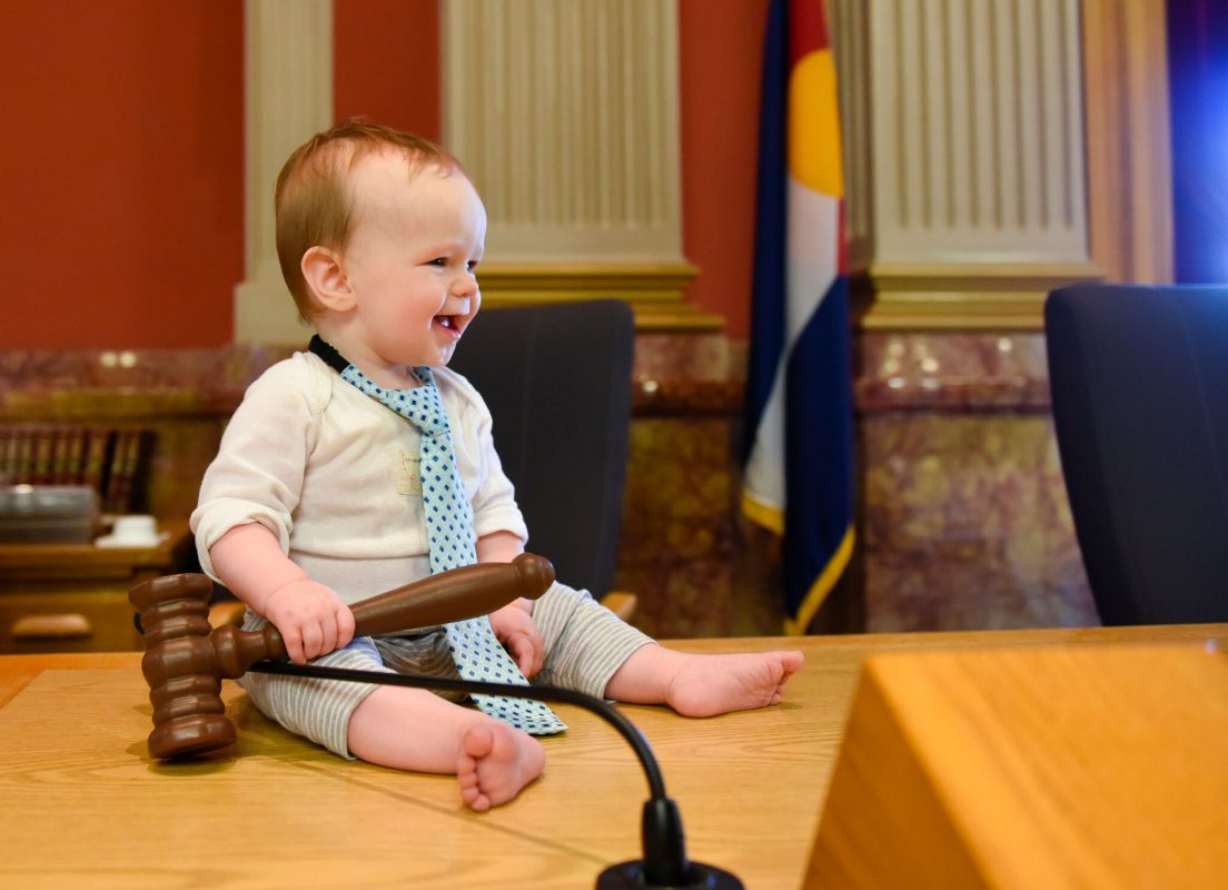 baby holding a gavel, wearing a tie in the state capitol senate chamber