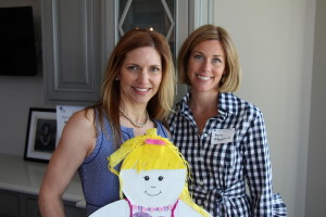 Circle of Friends Board Member Jen Rettig with Circle of Friends member Mary Fitzpatrick hold a doll decorated by a Colorado child for the Children's Campaign's signature Doll Day project.