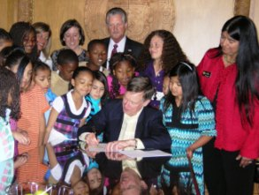 Gov. Hickenlooper signs HB-1069, surrounded by children and advocates.