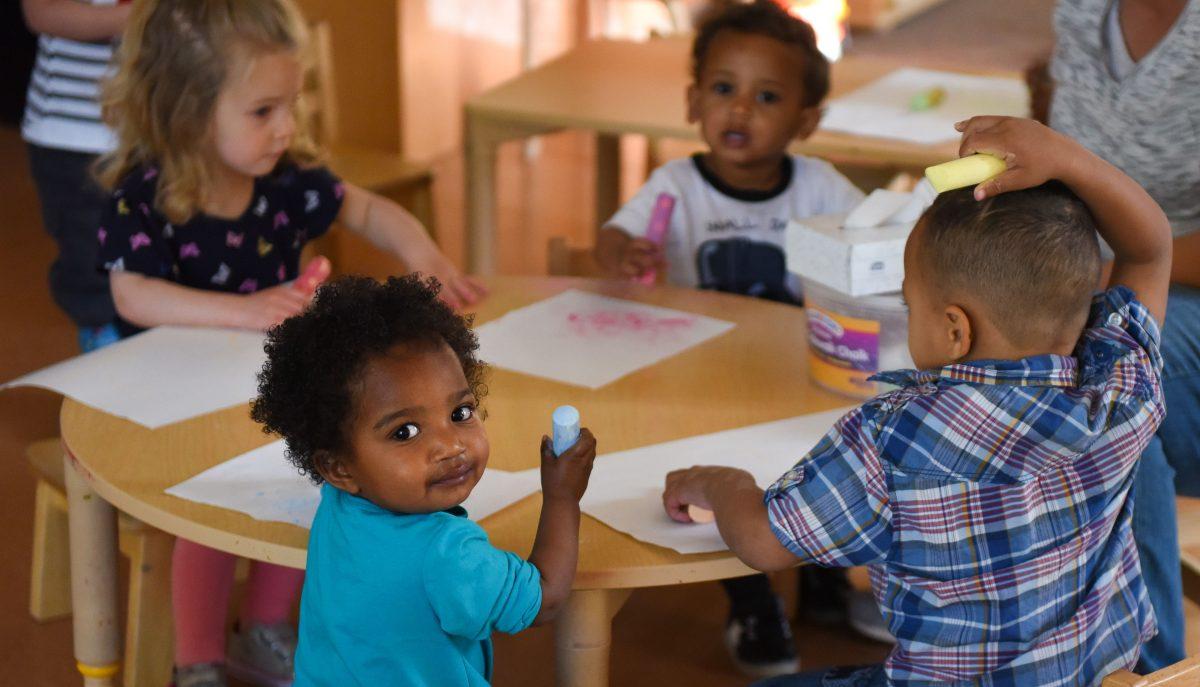 Un grupo de niños en un aula alrededor de una mesa