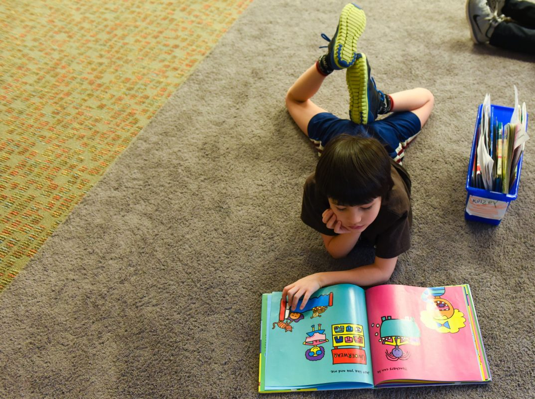 a boy reading a book on a carpet