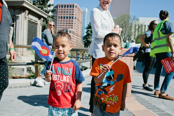Two young boys at the Colorado state capitol, waving Colorado flags
