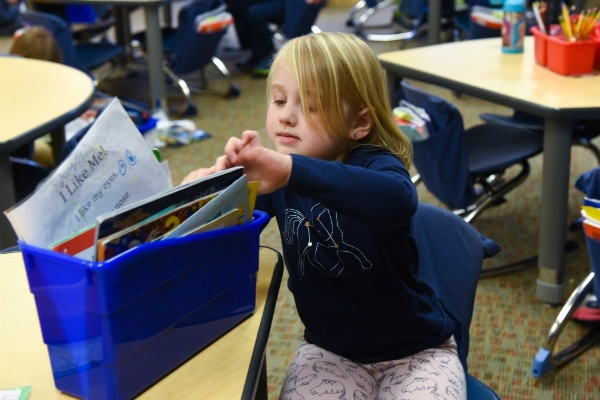 A child pulling a book out of a blue box